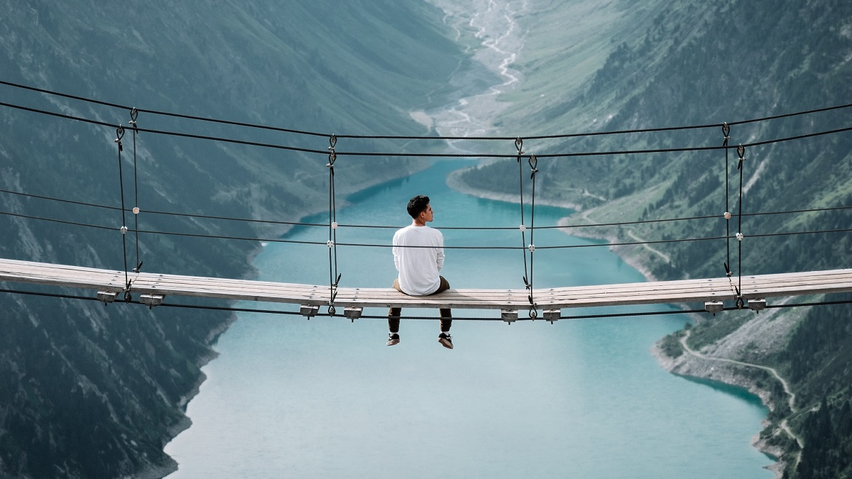 A lone man sits on a bridge.