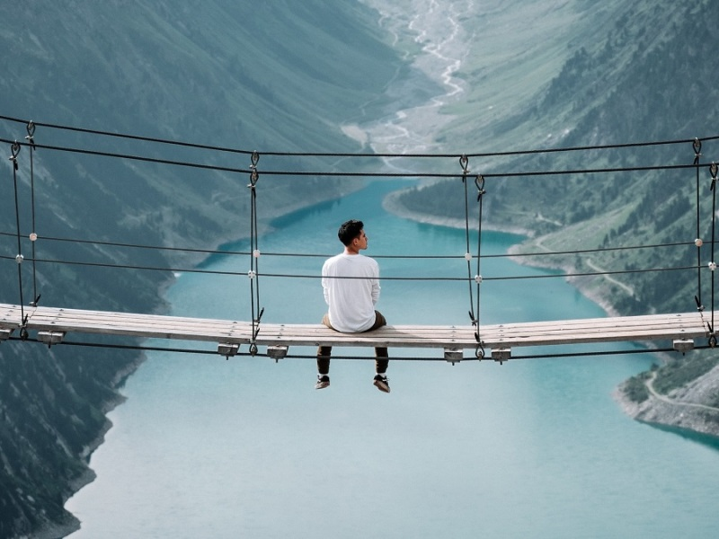 A lone man sits on a bridge.